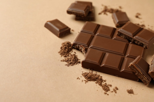 Tasty chocolate bar and powder on beige background