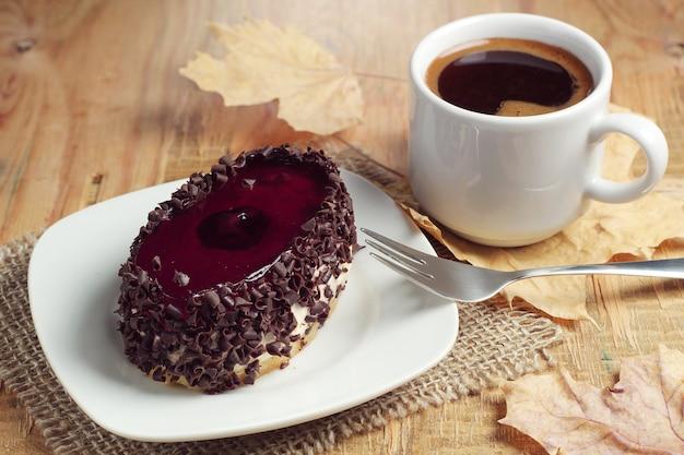 단풍잎이 있는 소박한 나무 테이블에 맛있는 초콜릿 케이크와 뜨거운 커피 한 잔