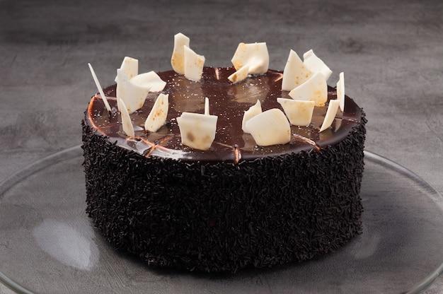 Вкусный шоколадный торт, украшенный кондитерской начинкой и кусочками белого шоколада