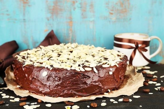 古い木製のテーブルの上に、アーモンドとおいしいチョコレートケーキ