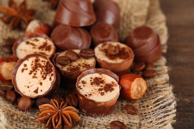Вкусные шоколадные конфеты с кофейными зернами и орехами на деревянном столе