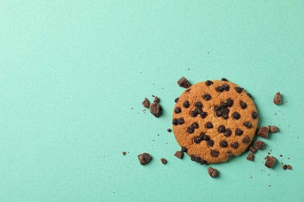 Tasty chocolate chip cookie on mint background