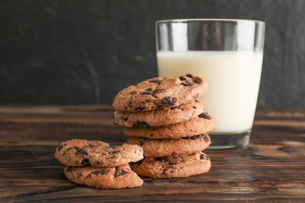 おいしいチョコレートチップクッキーと木製のテーブルに牛乳のガラス。テキストのためのスペース