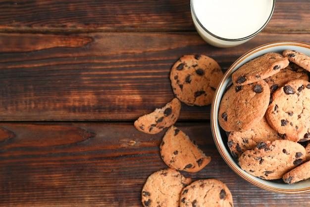 おいしいチョコレートチップクッキーと木製のテーブル、上面に牛乳のガラス。テキストのためのスペース