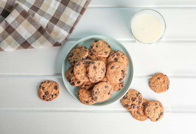 おいしいチョコレートチップクッキーと木製のテーブルに牛乳のガラス