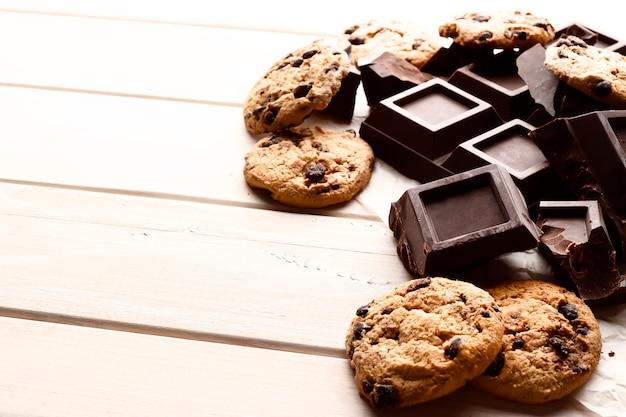 흰색 나무 배경에 맛있는 초콜릿 칩 쿠키와 블랙 초콜릿 조각. 텍스트에 대 한 장소입니다. 평면도.