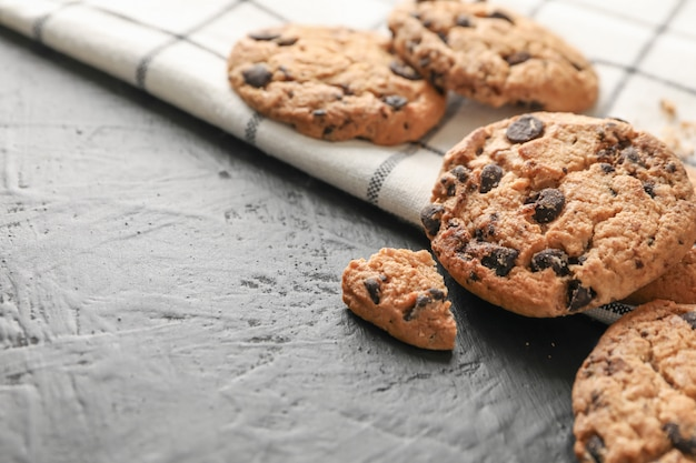 Tasty chocolate chip cookies on napkin and wooden background. space for text
