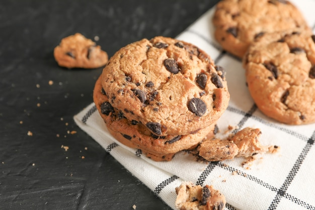 Tasty chocolate chip cookies on napkin and wooden background