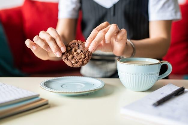 Вкусное шоколадное печенье в женских руках, держа его над блюдцем во время перерыва на кофе на рабочем месте