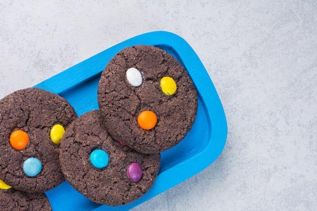 大理石の木製プレートにおいしいチョコレートクッキー。