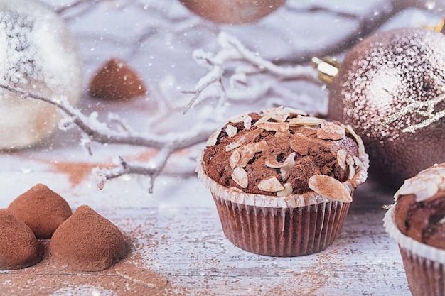 白い素朴な木製のテーブルにスイーツと冬の装飾が施されたおいしいチョコレートカップケーキ。冬の休日の背景。