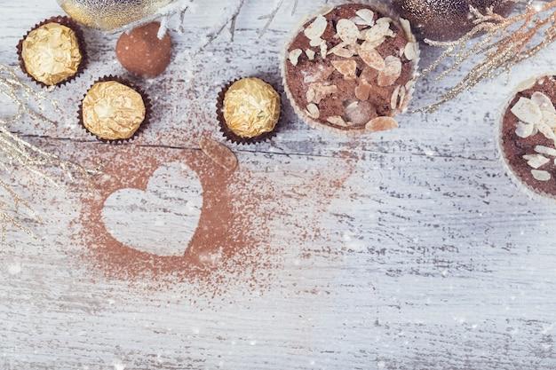 白い素朴な木製のテーブルにスイーツ、ハート型のココアパウダー、冬の装飾が施されたおいしいチョコレートカップケーキ。冬の休日の背景。テキスト用のコピースペースを備えたフラットレイ。