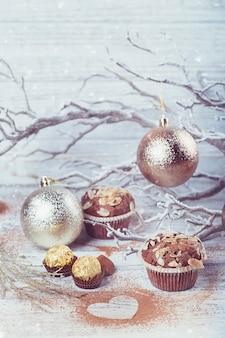 白い素朴な木製のテーブルにスイーツ、ハート型のココアパウダー、冬の装飾が施されたおいしいチョコレートカップケーキ。冬の休日の背景。