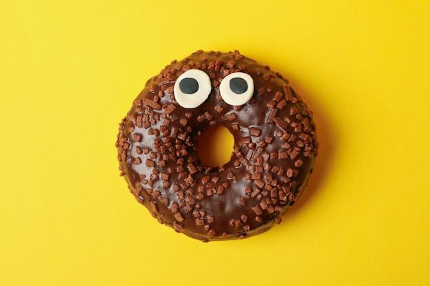 Вкусный шоколадный пончик с глазами на желтом фоне