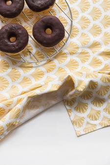 Tasty chocolate donuts on metal rack on table cloth over the white background