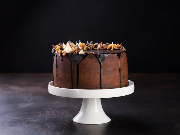 Tasty chocolate drip cake with melting chocolate on dark
