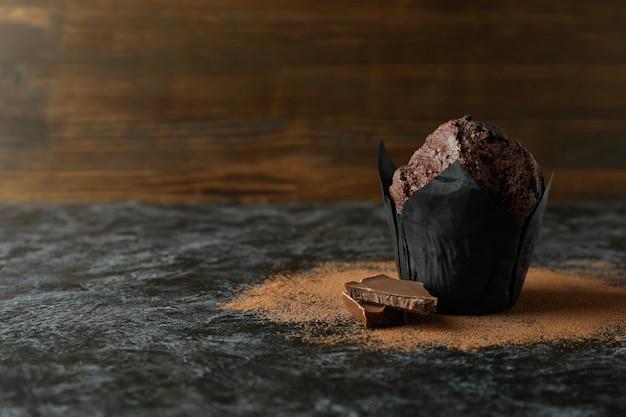 Tasty chocolate muffin on black smokey table.