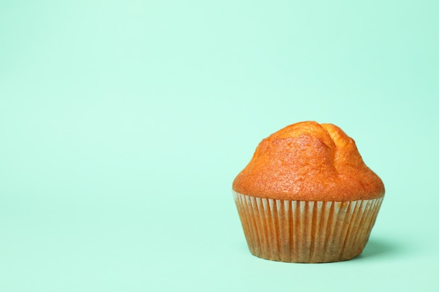 Tasty chocolate muffin on mint background, space for text