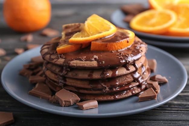 甘いソースとスライスしたオレンジのプレートにおいしいチョコレートパンケーキ