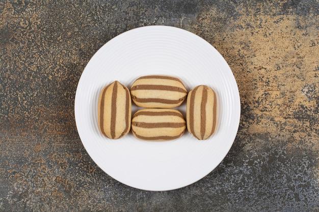 하얀 접시에 맛있는 초콜릿 스트라이프 비스킷.