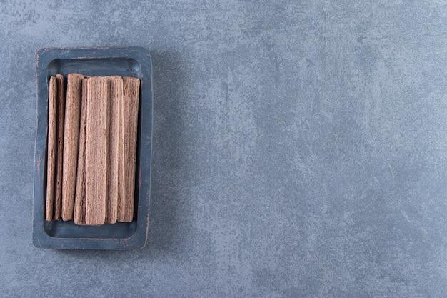Вкусный шоколадный вафельный рулет в деревянной тарелке на мраморном фоне.