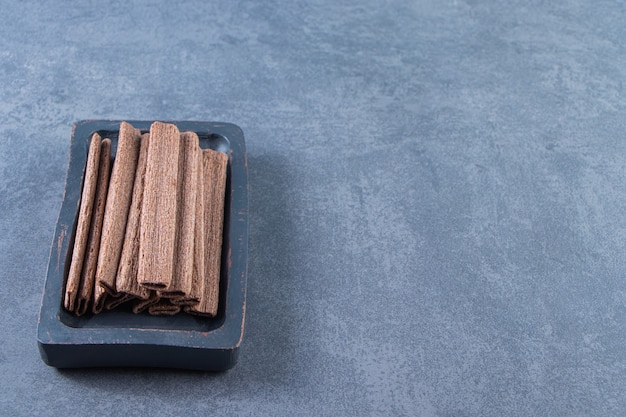 Tasty chocolate wafer roll in a wooden plate , on the marble background.