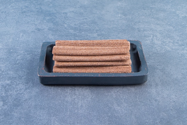 Tasty chocolate wafer roll in a wooden plate on the marble surface