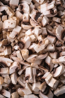 Tasty chopped champignon mushrooms texture, uncooked food sliced, dark brown wooden table, top view macro