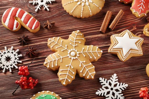 Вкусное рождественское печенье и декор на деревянном столе, вид крупным планом
