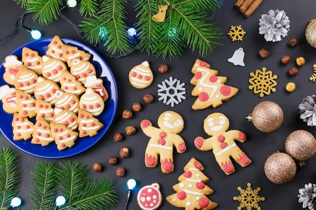 おいしいクリスマスクッキー、クリスマスツリー、黒の背景に装飾。クリスマス料理のコンセプト。上面図