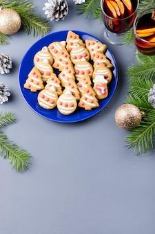 おいしいクリスマスクッキー、ギフトボックス、クリスマスツリーと黒の背景にライトが付いた装飾。上面図