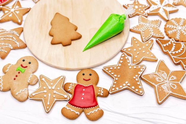 Вкусные рождественские пряники с украшениями на разделочной доске