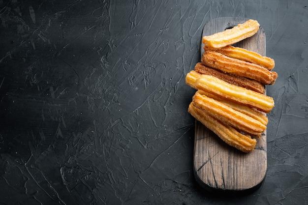 텍스트를 위한 공간이 있는 검정색 배경에 초콜릿 카라멜 소스 세트가 있는 맛있는 추로, 카피스페이스