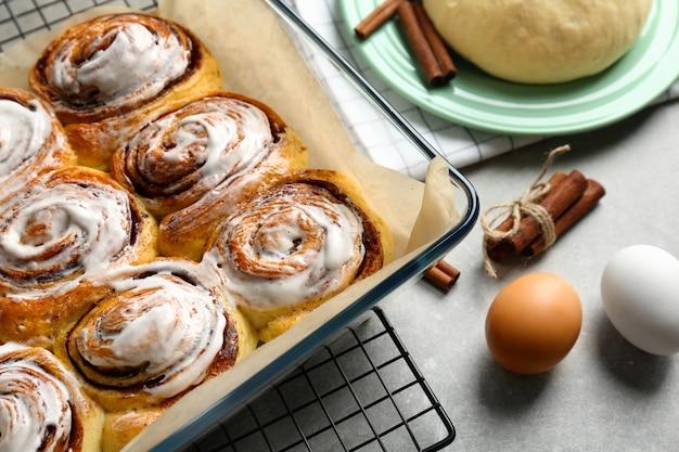 Вкусные булочки с корицей в форме для выпечки на столе