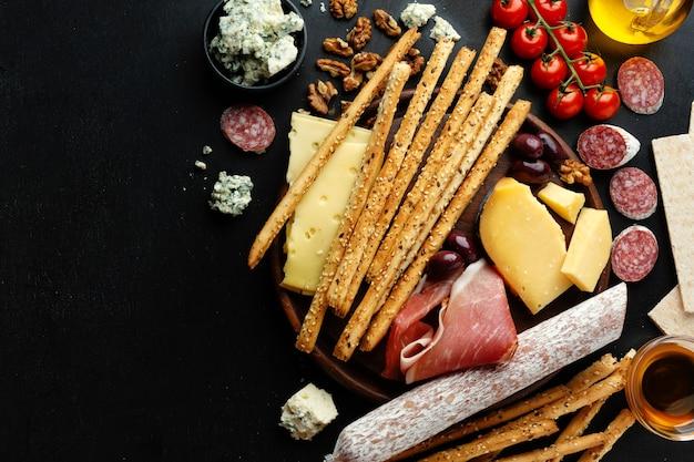 Tasty classic italian appetizers on dark surface