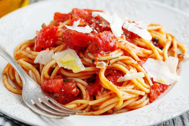 Вкусная классическая итальянская паста с томатным соусом и сыром на тарелке. крупный план.