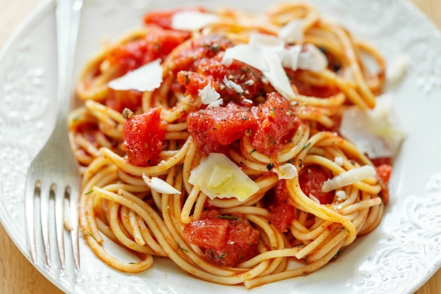 Tasty classic italian pasta with tomato sauce and cheese on plate. closeup.