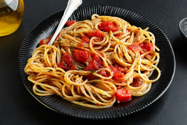 Tasty classic italian pasta with tomato sauce and cheese on plate on dark background. top view.