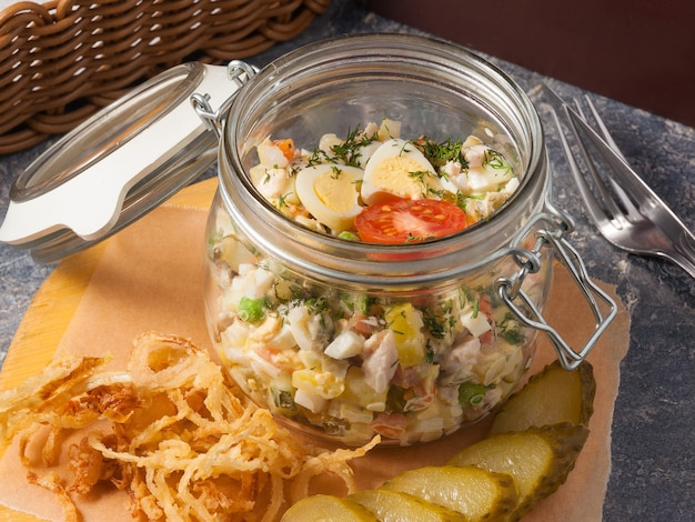 Tasty classic olivier salad in a jar unusual serving in a restaurant