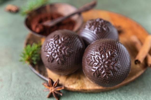 전나무 가지와 향신료가 있는 나무 접시에 마시멜로와 초콜릿을 넣은 맛있는 코코아 폭탄. 트렌디한 겨울 뜨거운 음료. 선택적 초점입니다. 확대.