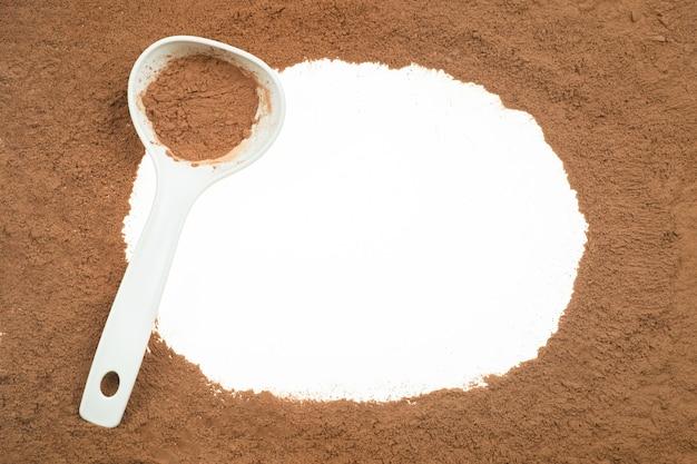 Вкусный какао-порошок в ложке изолированной на белой предпосылке.