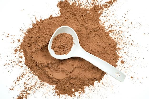 Вкусный какао-порошок в ложке изолированной на белой стене.