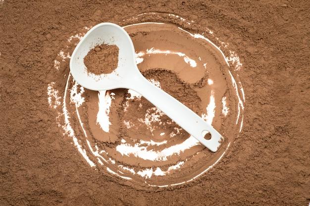 Вкусный какао-порошок в ложке изолированной на белизне.