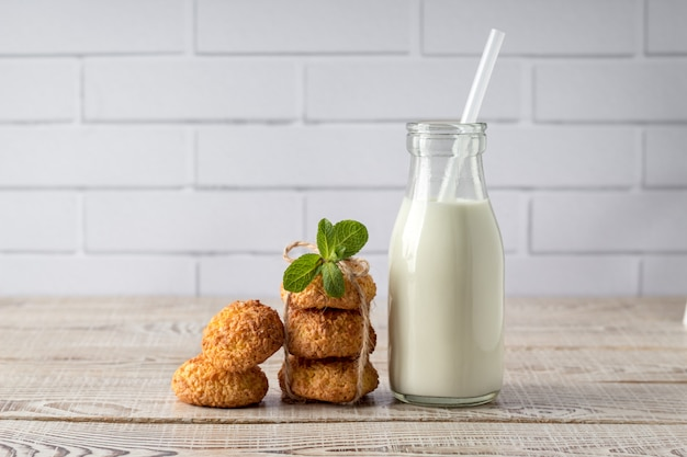 Tasty coconut cookies and bottle of milk on white wooden table