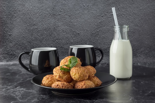Tasty coconut cookies and drinks on dark marble table