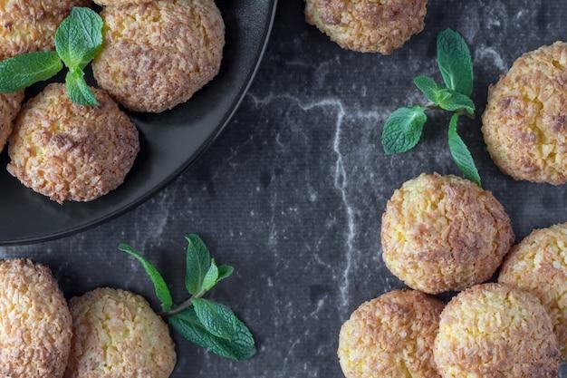 Вкусное кокосовое печенье на темном мраморном столе, плоская планировка