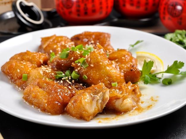 Вкусная треска в медовом соусе на белой тарелке китайская кухня