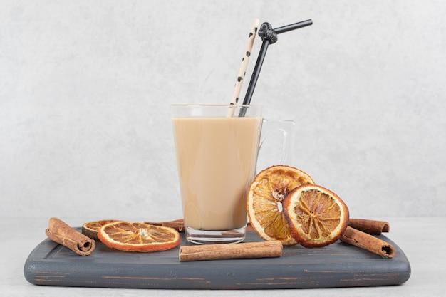 Вкусный кофе, палочки корицы и дольки апельсина на темной тарелке