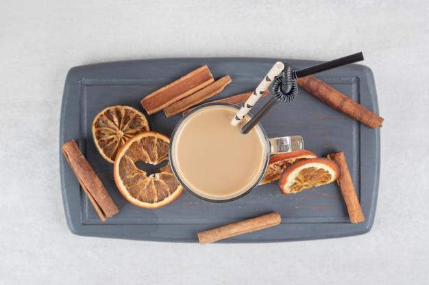 어두운 접시에 맛있는 커피, 계피 스틱 및 오렌지 슬라이스