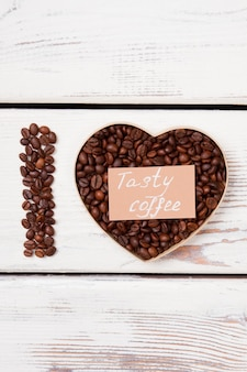 Tasty coffee love concept. coffee beans in a shape of heart and letter i. white wood surface.